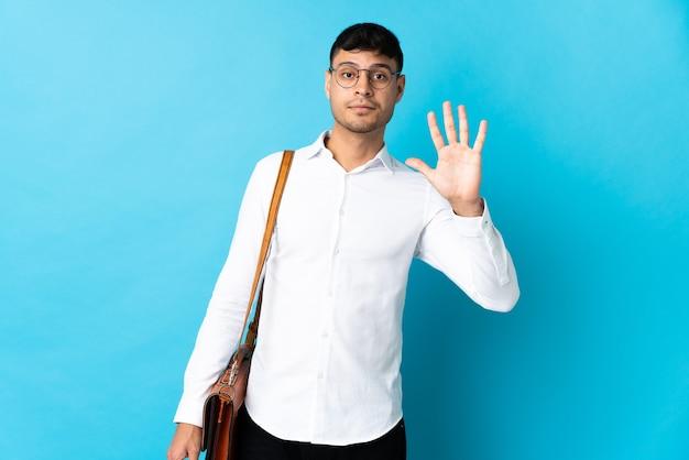 Giovane uomo colombiano di affari isolato sull'azzurro che conta cinque con le dita