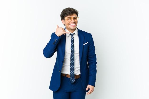 Uomo freddo di giovani affari che mostra un gesto di chiamata di telefono cellulare con le dita.