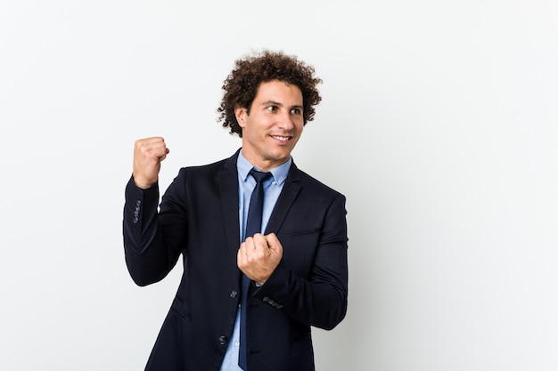 Uomo riccio di giovani affari contro fondo bianco che alza pugno dopo una vittoria, concetto del vincitore.