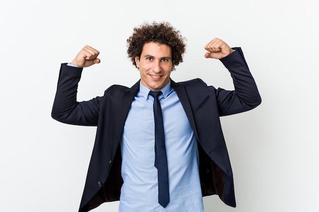 Uomo riccio di giovani affari contro fondo bianco che mostra gesto di forza con le armi, simbolo di potere femminile