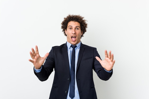 Uomo d'affari giovane riccio contro il muro bianco che celebra una vittoria o un successo, è sorpreso e scioccato.