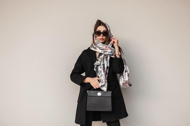 Giovane donna di moda di affari in occhiali da sole alla moda in un cappotto nero con una borsa di cuoio alla moda in sciarpa di fascino che posa vicino a una parete d'annata sulla via. attraente ragazza alla moda. signora elegante.