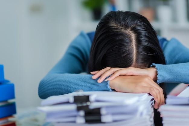 Femmina giovane business dormendo al tavolo della scrivania, provato donna attrattiva con una pila di carte.