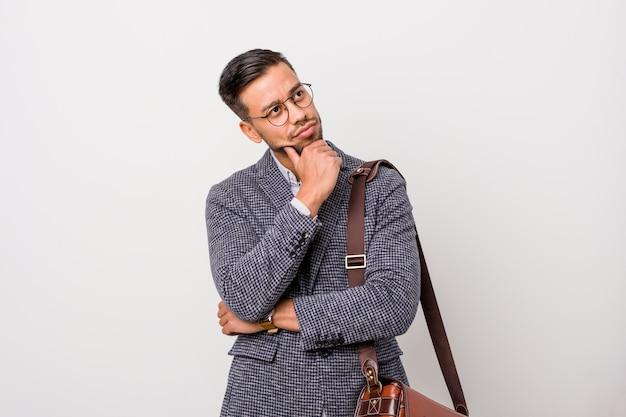Uomo filippino di giovani affari contro una parete bianca che guarda lateralmente con espressione dubbiosa e scettica.