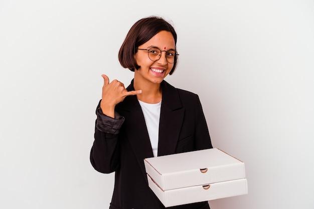 Giovane donna indiana di affari che tiene le pizze isolate che mostrano un gesto di chiamata di telefono cellulare con le dita.