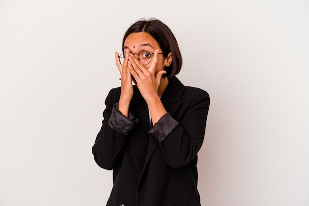 Giovane donna indiana di affari isolata su bianco lampeggia attraverso le dita spaventata e nervosa.