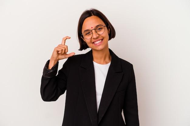 Giovane donna indiana di affari isolata su bianco che tiene qualcosa di poco con gli indici, sorridente e sicura.