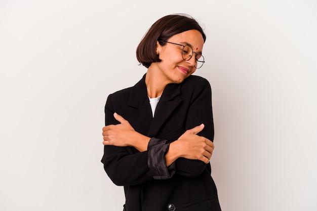 Giovane donna indiana di affari isolata sugli abbracci bianchi, sorridente spensierata e felice.