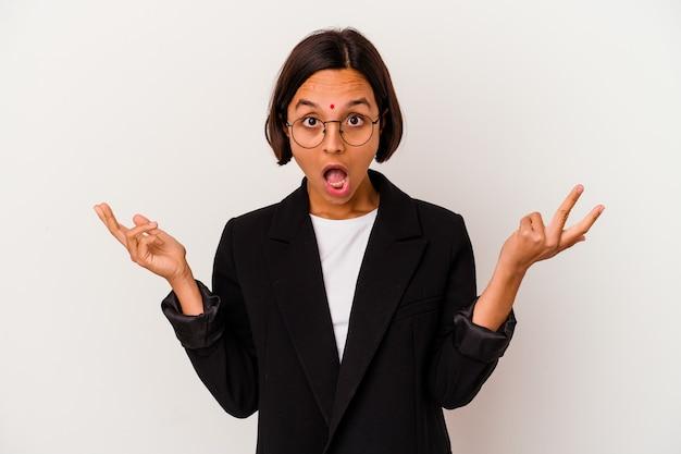 Giovane donna indiana di affari isolata su bianco sorpreso e scioccato.
