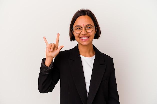 Giovane donna indiana di affari isolata sul muro bianco che mostra un gesto di corna come un concetto di rivoluzione.