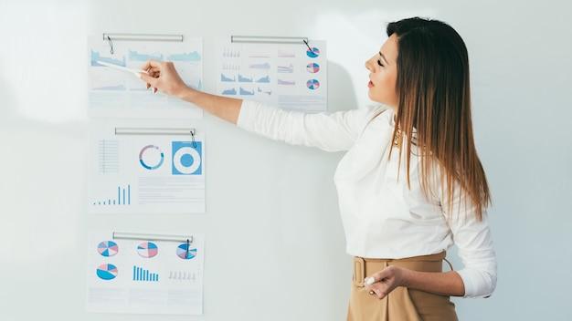Giovane donna d'affari che fa presentazione. rapporto di analisi finanziaria