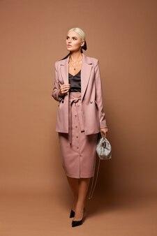 Una giovane donna d'affari in abiti alla moda, con la camicetta nera e l'abito beige che guarda da parte e posa sullo sfondo beige