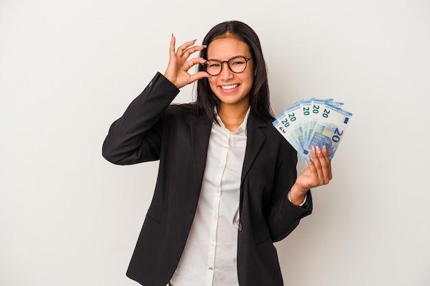 Giovane donna d'affari latina che tiene bollette caffè isolato su sfondo bianco eccitato mantenendo il gesto ok sull'occhio.