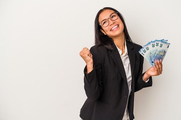Giovane donna d'affari latina che tiene bollette caffè isolato su sfondo bianco punta con il dito pollice lontano, ridendo e spensierato.