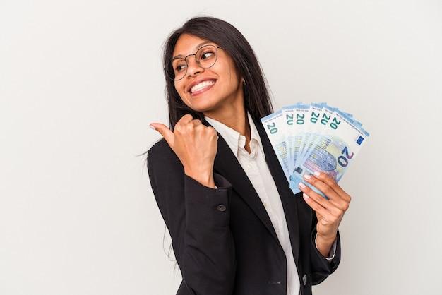 Giovane donna d'affari latina che tiene le fatture isolate su sfondo bianco indica con il dito pollice lontano, ridendo e spensierato.