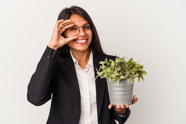 La giovane donna latina di affari che tiene le piante isolate su fondo bianco ha eccitato mantenendo il gesto giusto sull'occhio.