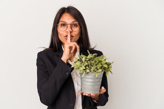 Giovane donna d'affari latina che tiene piante isolate su sfondo bianco mantenendo un segreto o chiedendo silenzio.
