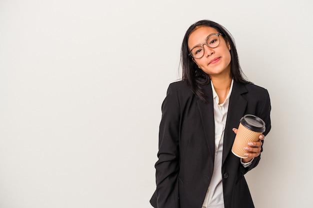 La giovane donna latina d'affari che tiene un caffè da asporto isolato su sfondo bianco confuso, si sente dubbiosa e insicura.