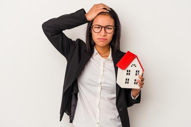 Giovane donna d'affari latina in possesso di una casa giocattolo isolata su sfondo bianco scioccata, ha ricordato un incontro importante.