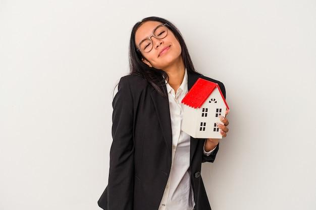 Giovane donna latina d'affari che tiene una casa giocattolo isolata su sfondo bianco sognando di raggiungere obiettivi e scopi
