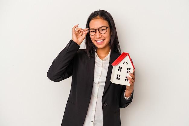 La giovane donna latina di affari che tiene una casa del giocattolo isolata su fondo bianco ha eccitato mantenendo il gesto giusto sull'occhio.