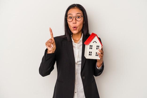 Giovane donna latina di affari che tiene una casa del giocattolo isolata su fondo bianco che ha qualche grande idea, concetto di creatività.