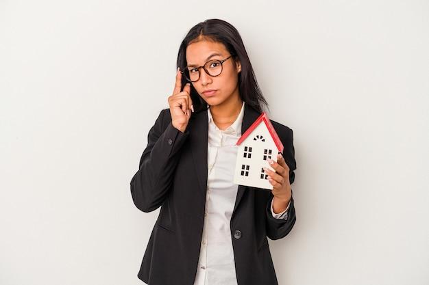 Giovane donna latina d'affari in possesso di una casa giocattolo isolata su sfondo bianco che punta al tempio con il dito, pensando, focalizzato su un compito.