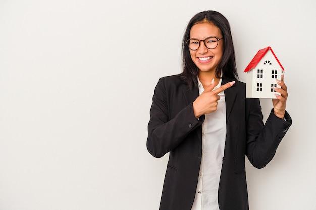 Giovane donna latina di affari che tiene una casa del giocattolo isolata su fondo bianco che sorride e che indica da parte, mostrando qualcosa allo spazio vuoto.