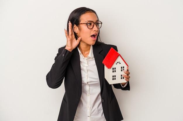 Giovane donna latina di affari che tiene una casa del giocattolo isolata su fondo bianco che prova ad ascoltare un gossip.