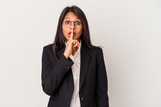 Giovane donna latina d'affari isolata su sfondo bianco mantenendo un segreto o chiedendo silenzio.