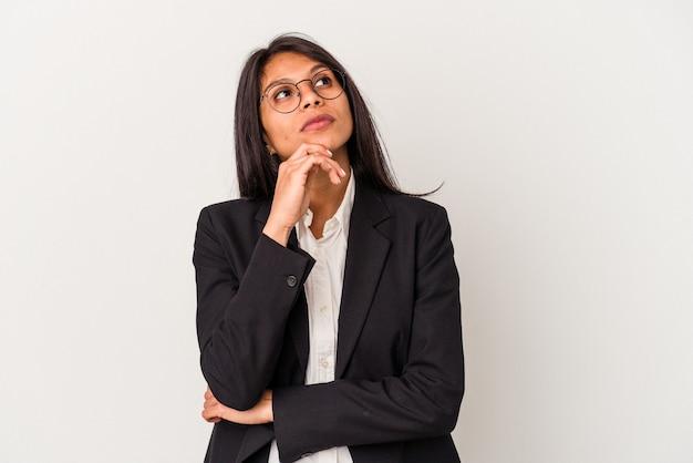 Giovane donna latina d'affari isolata su sfondo bianco guardando lateralmente con espressione dubbiosa e scettica.