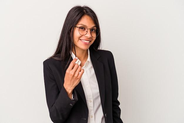 Giovane donna latina d'affari isolata su sfondo bianco che punta con il dito su di te come se invitasse ad avvicinarsi.