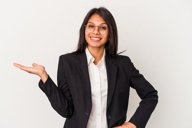 Giovane donna latina di affari isolata su fondo bianco che mostra uno spazio della copia su una palma e che tiene un'altra mano sulla vita.
