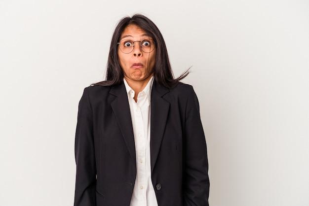 La giovane donna latina di affari isolata su fondo bianco alza le spalle e apre gli occhi confusi.