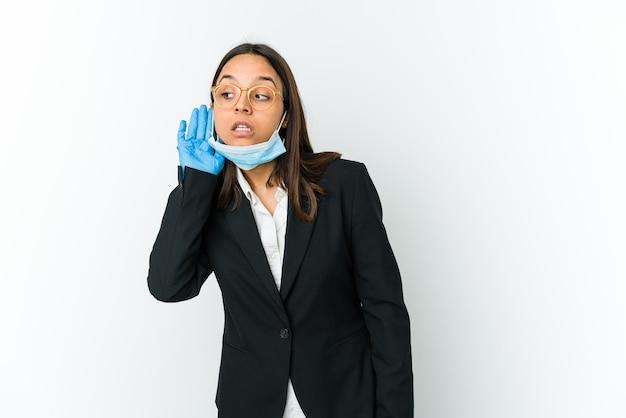 Giovane donna latina di affari che indossa una maschera per proteggere da covid isolato su bianco cercando di ascoltare un pettegolezzo.