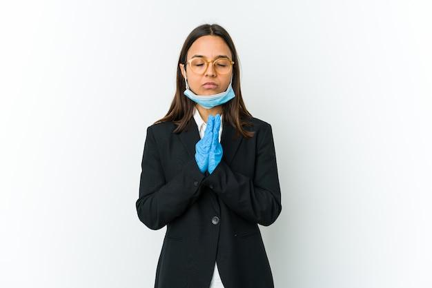 Giovane donna latina di affari che indossa una maschera per proteggere da covid isolato sul muro bianco che tiene le mani in preghiera vicino alla bocca, si sente sicura.