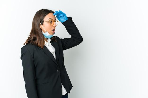Giovane donna latina di affari che indossa una maschera per proteggere da covid isolato sul muro bianco che guarda lontano tenendo la mano sulla fronte.