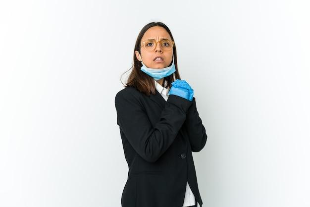Giovane donna latina di affari che indossa una maschera per proteggere da covid isolato sul muro bianco spaventato e impaurito.