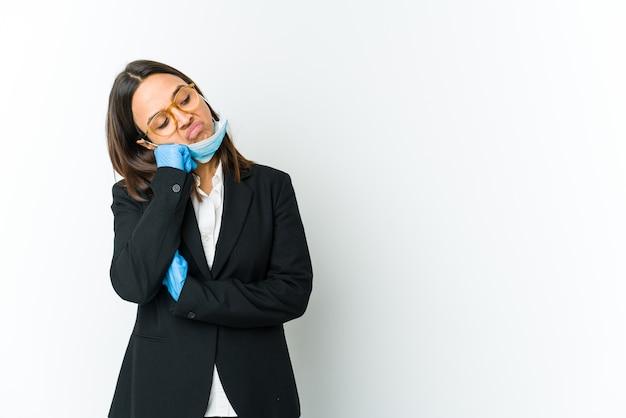 Giovane donna latina di affari che indossa una maschera per proteggere da covid isolato sul muro bianco che si sente triste e pensieroso, guardando lo spazio della copia.