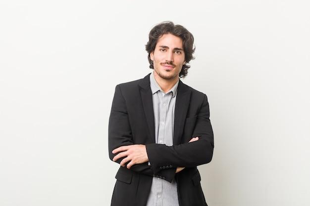 Giovane uomo d'affari su uno sfondo bianco che si sente fiducioso, incrociando le braccia con determinazione.