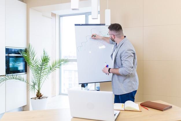 Giovane uomo d'affari in abiti casual riunione online presentazione o formazione utilizzando una webcam portatile e una lavagna a fogli mobili con pennarelli