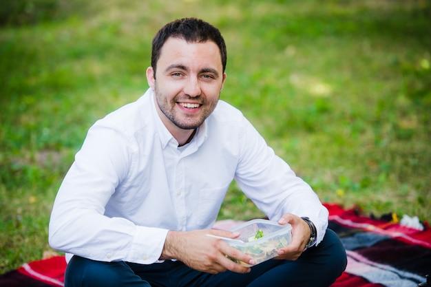 Giovane uomo di affari che gode del cibo che ha portato in un pranzo al sacco da casa