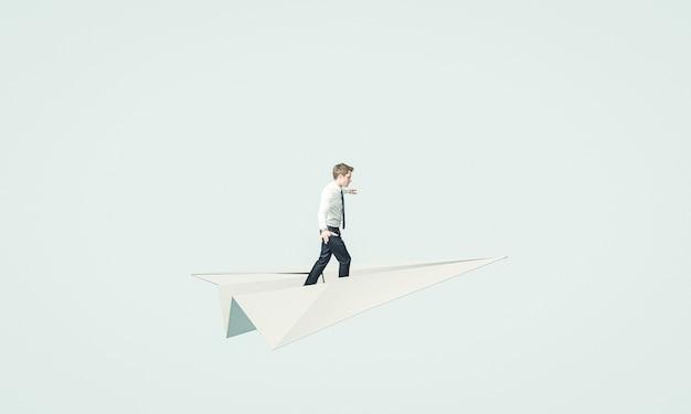 Giovane uomo d'affari vola su un aeroplano di carta.