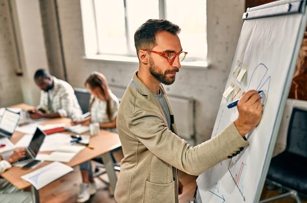 Giovane uomo d'affari in bicchieri disegna con un pennarello su una lavagna in un ufficio moderno.