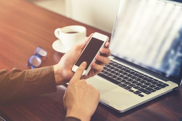 Giovane uomo d'affari azienda mano e utilizzando il telefono in ufficio con la luce del sole. filtro tonico vintage.
