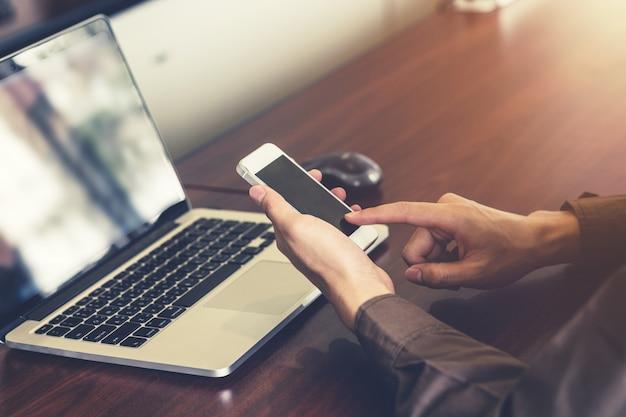 Giovane uomo d'affari azienda mano e utilizzando smartphone in ufficio con la luce del sole. filtro tonico vintage.