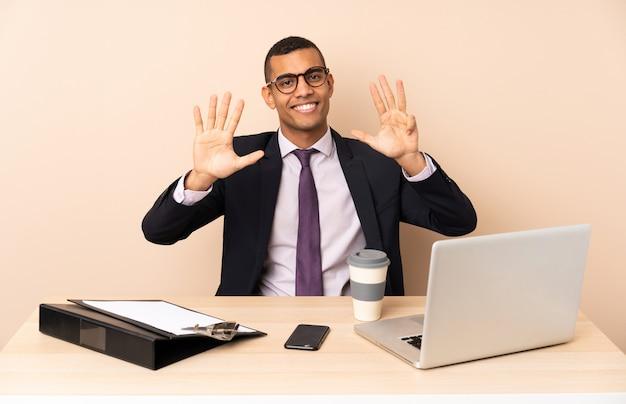 Uomo d'affari giovane nel suo ufficio con un computer portatile e altri documenti contando nove con le dita