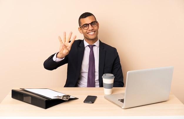 Uomo d'affari giovane nel suo ufficio con un computer portatile e altri documenti felici e contando quattro con le dita