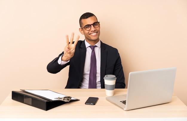 Uomo d'affari giovane nel suo ufficio con un computer portatile e altri documenti felici e contando tre con le dita