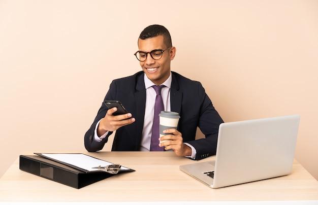 Uomo d'affari giovane nel suo ufficio con un computer portatile e altri documenti in possesso di caffè da portare via e un cellulare